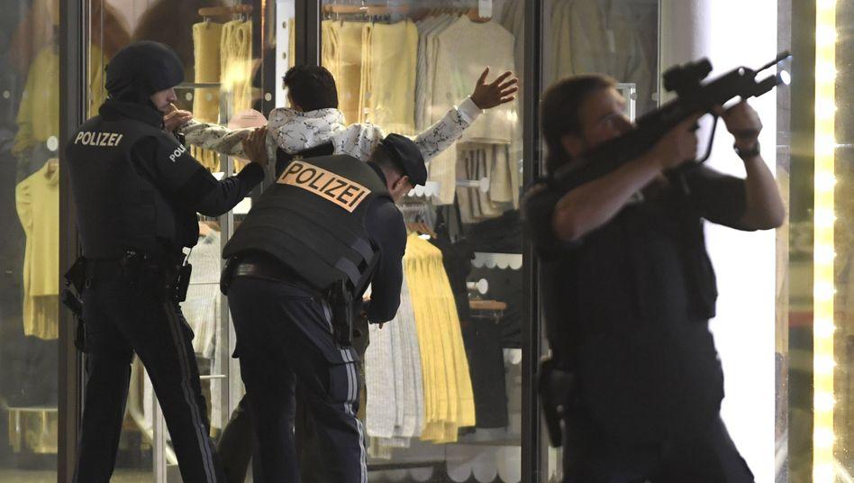 Polizisten kontrollieren eine Person nach dem Anschlag in Wien