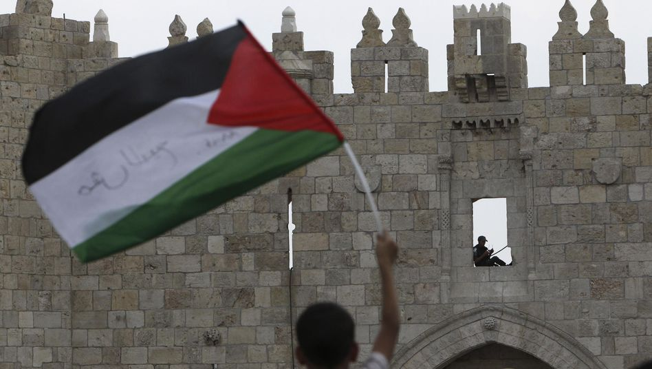 A Palestinian boy waves a flag in Jerusalem's Old City as an Israeli police officer looks on.