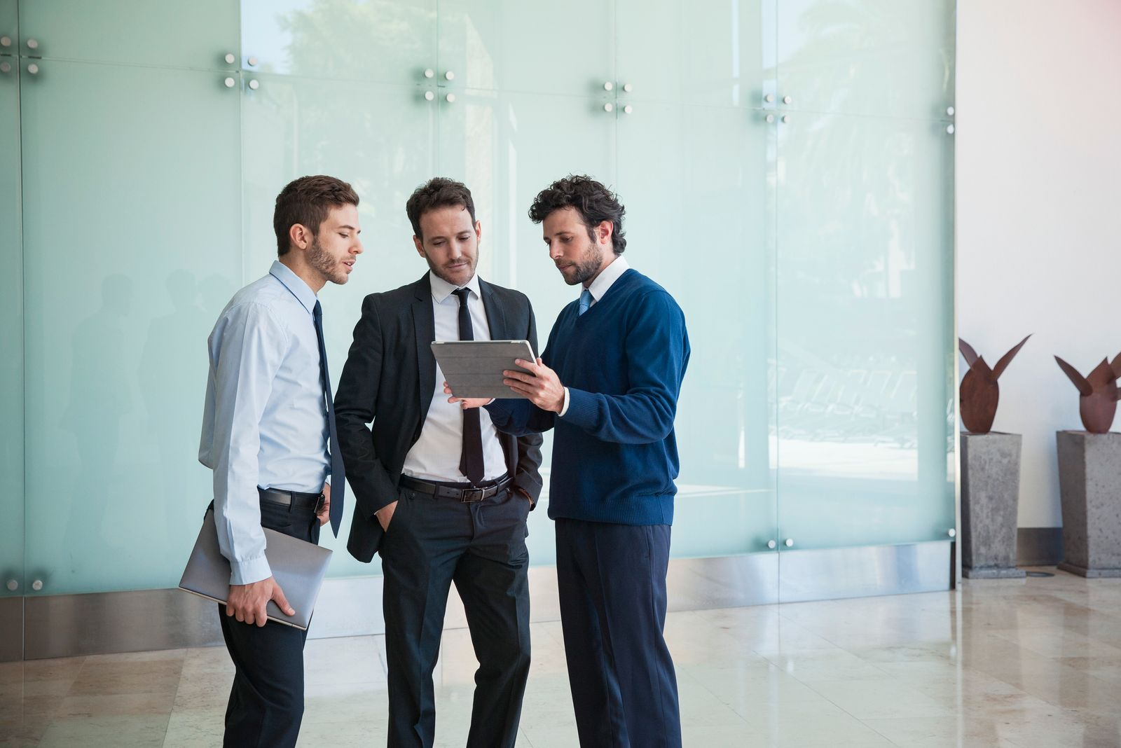 Businessman presenting idea to associates using digital tablet