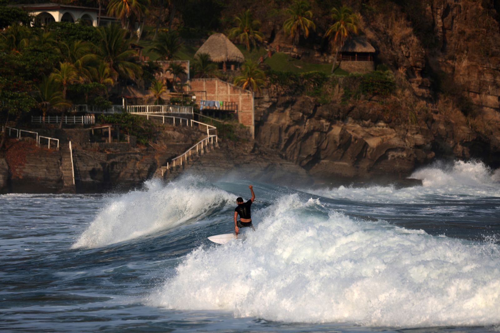 A surfer rides a wave at El Zonte Beach in Chiltuipa