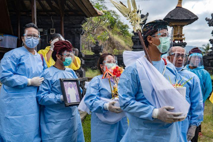 """Balinesen tragen Schutzanzüge während einer hinduistischen Feuerbestattungszeremonie namens """"Ngaben"""""""