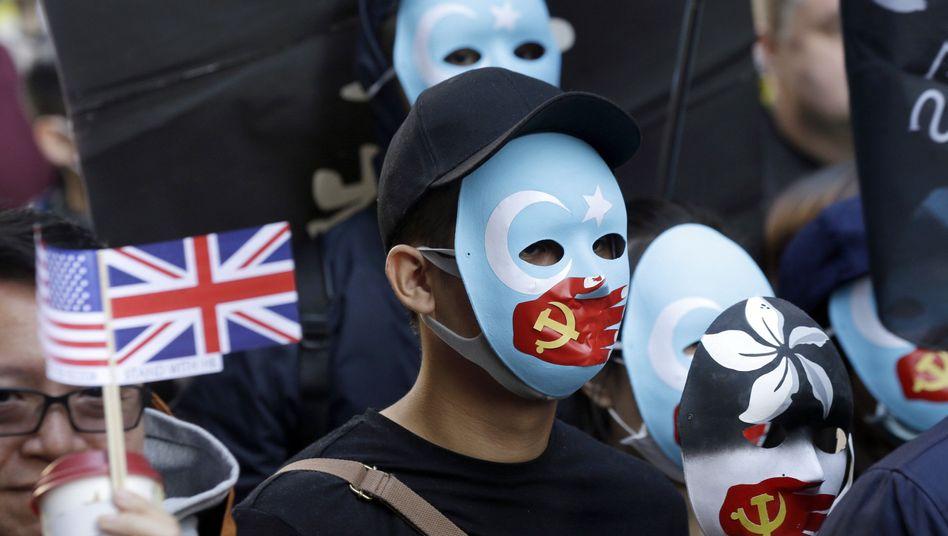Demonstranten tragen am Sonntag Masken, auf denen ihnen eine sowjetische Hand den Mund verbietet