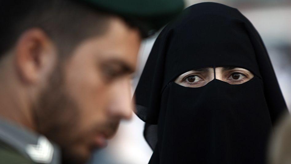 Eine verschleierte Palästinenserin wird am israelischen Kalandia-Grenzübergang kontrolliert