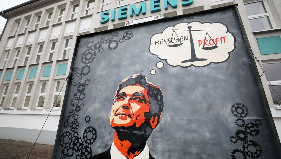 """Protestplakat mit dem Bild von Siemens-Chef Joe Kaeser vor dem Siemens-Turbomaschinen-Werk in Leipzig (Archivbild): """"Mit seiner Publicityshow hat Kaeser das Thema überhaupt erst so stark ins öffentliche Rampenlicht gerückt"""""""