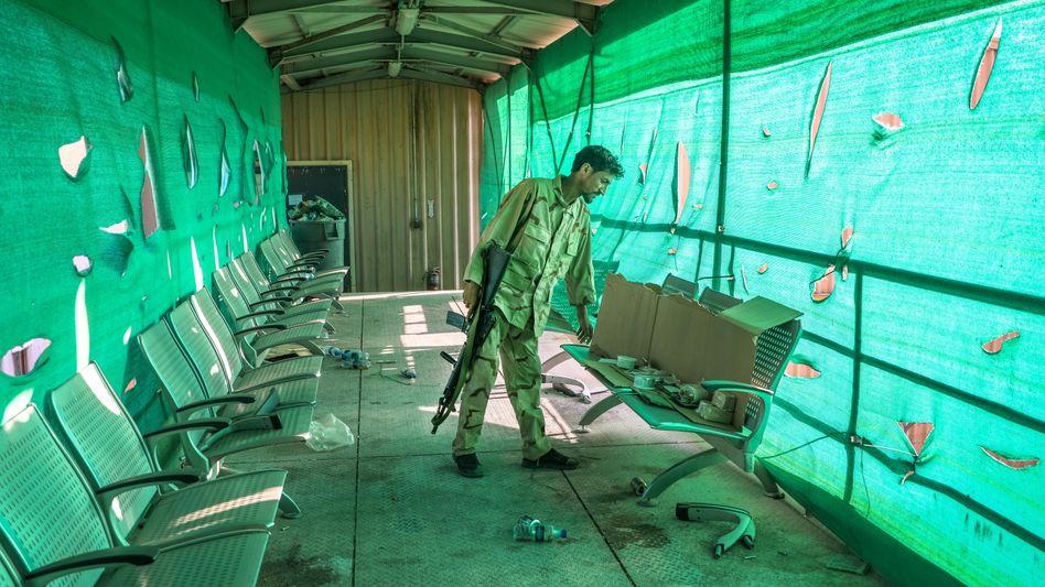 Ein afghanischer Soldat durchsucht von den US-Truppen zurückgelassene Kartons in Bagram