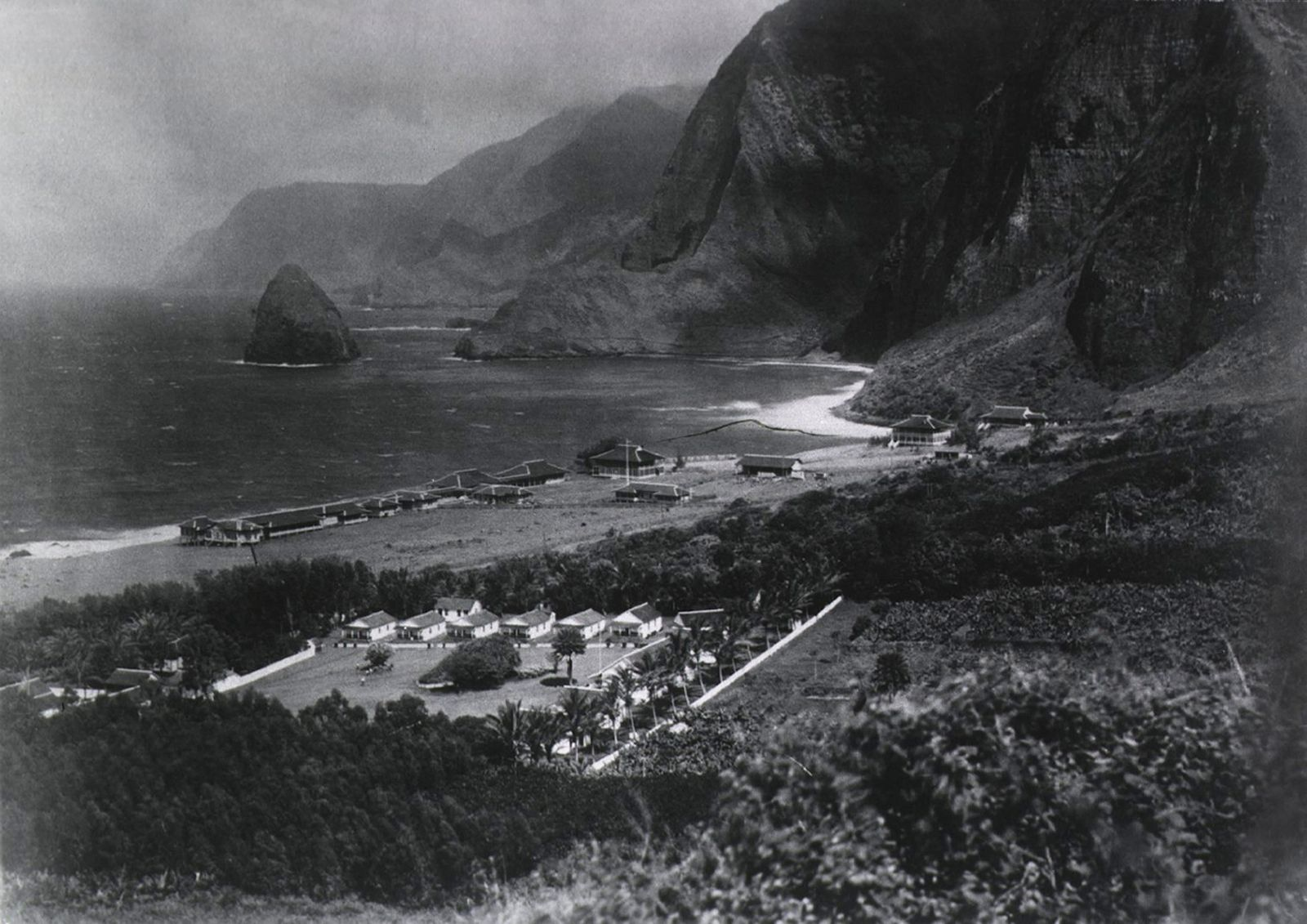 Leper Colony. The Kalawao Settlement, on the small Hawaiian island of Molokai, was established in 1866 as the first isolation settlement for Lepers. View of the Photo shows a circa 1900 view of the colony, showing buildings, ocean, and mountains. Kalawao i