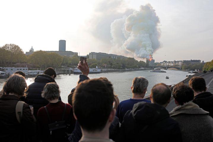 Menschen in Paris blicken am fr??hen Montagabend Richtung Notre-Dame