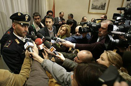 An Italian police officer answers journalists questions after a Romanian was arrested for allegedly raping and beating a 47-year old woman, who died on Thursday night.