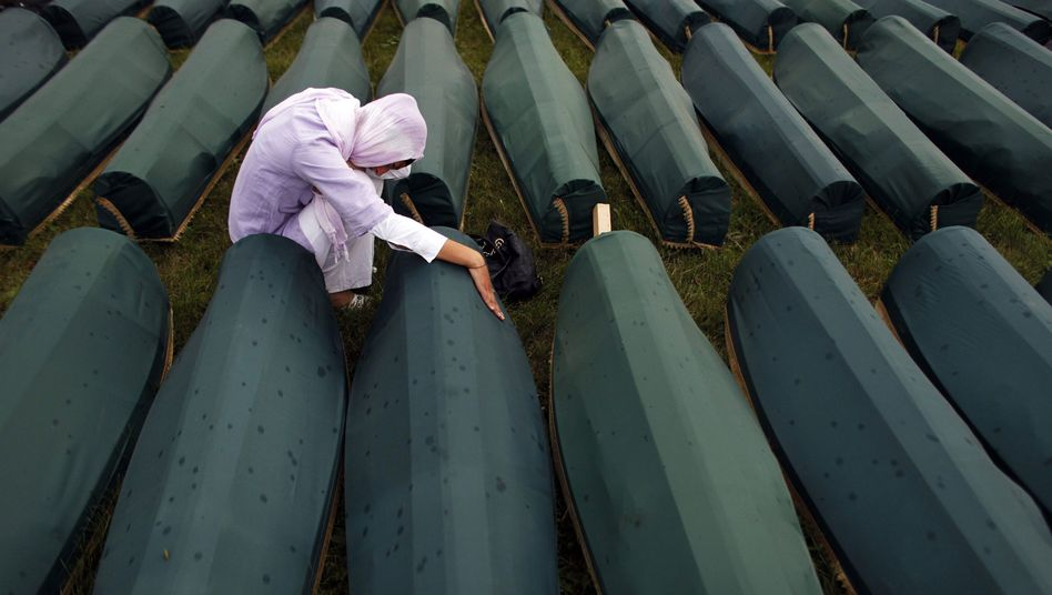 A Muslim woman praying next to newly identified victims of the Srebrenica massacre in July of last year. On Thursday, retired US General John J. Sheehan said that gays in the Dutch military were partly to blame for their failure to prevent the slaughter.