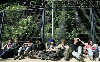 Anti-G-8 activists relax by the security fence Thursday.