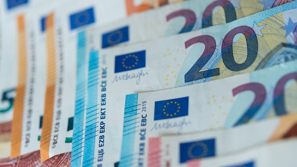 Banknoten auf einem Tisch (Symbolbild): Einnahmeplus dank Negativzins