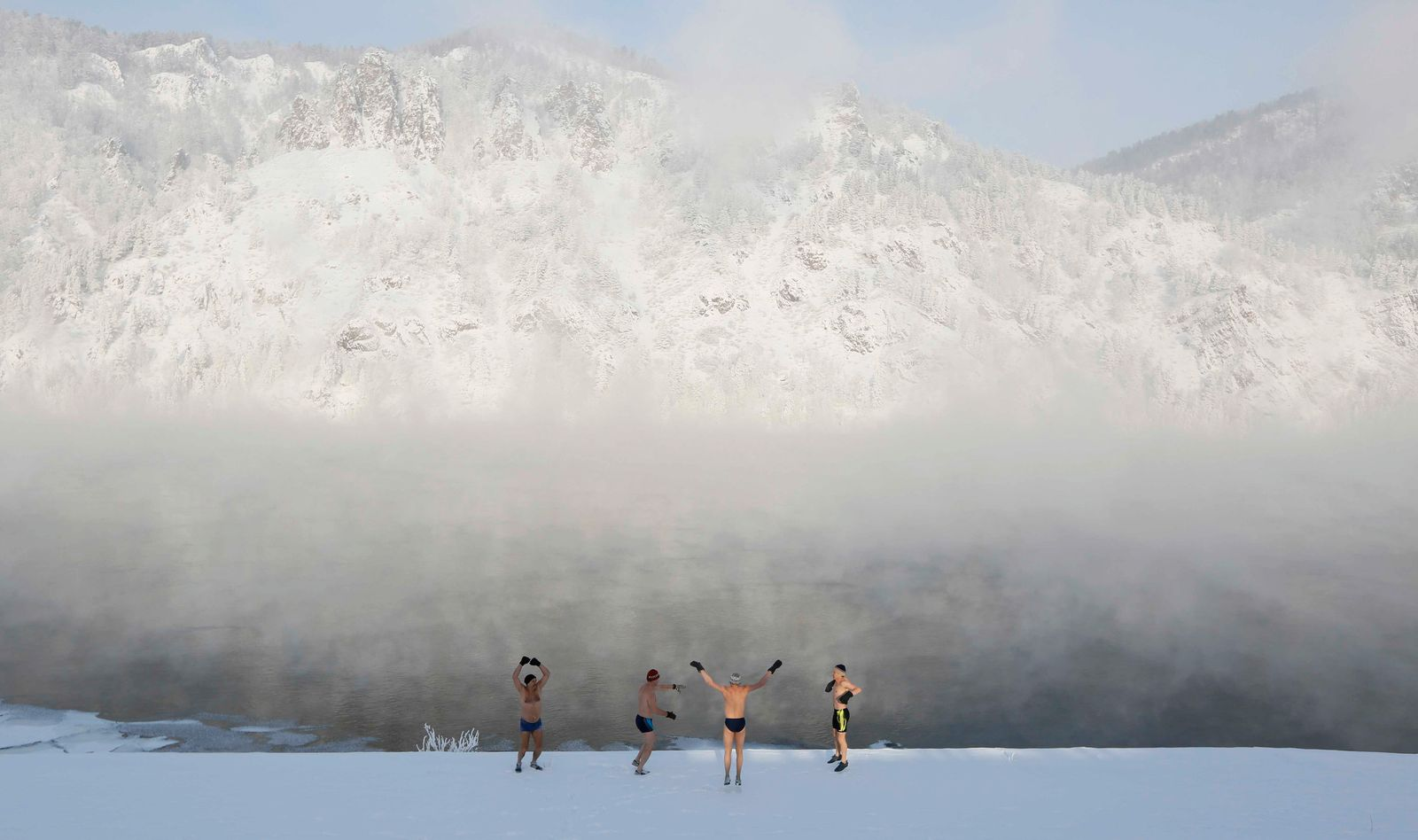 Members of the Dolphin winter swimming club warm up on the bank of the Yenisei River ahead of their weekly bathing session in Divnogorsk
