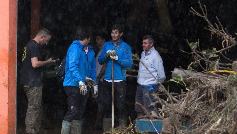 Rafael Nadal (2.v.r.) hilft bei den Aufräumarbeiten
