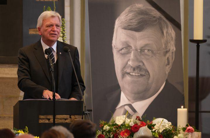 Volker Bouffier, Hessens Ministerpräsident, bei der Trauerfeier vor einem Porträt von Walter Lübcke