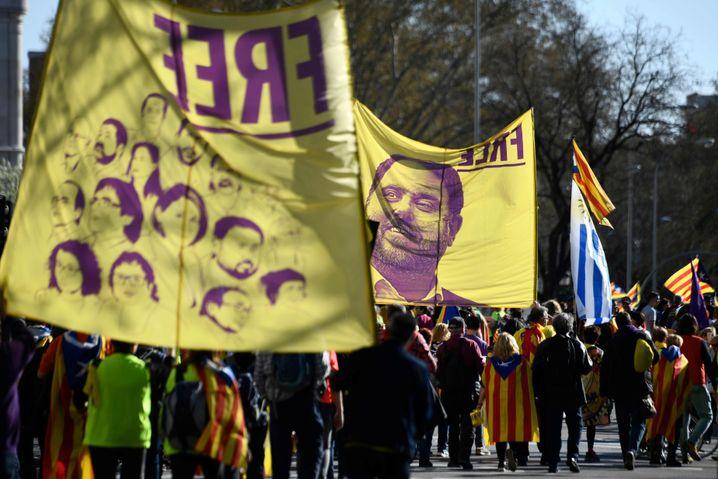 Demonstrierende tragen Banner mit Bildern der inhaftierten Separatisten in Madrid