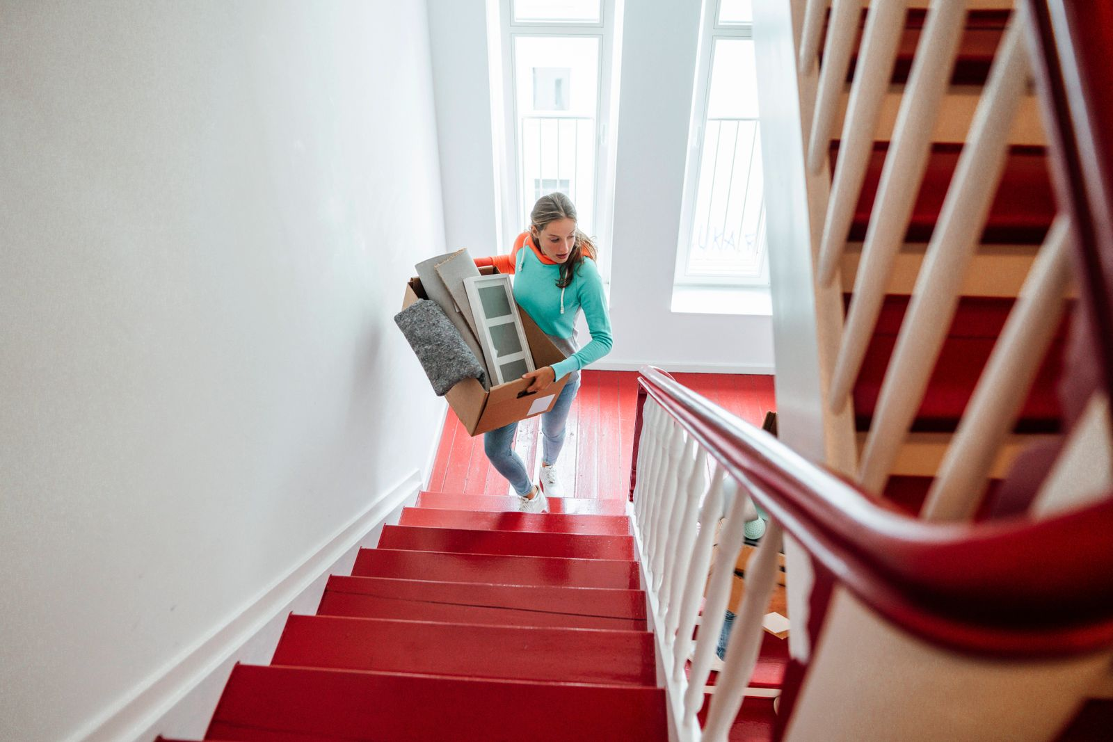 Young woman carrying cardboard boxes while moving up on staircase at home model released Symbolfoto property released JO