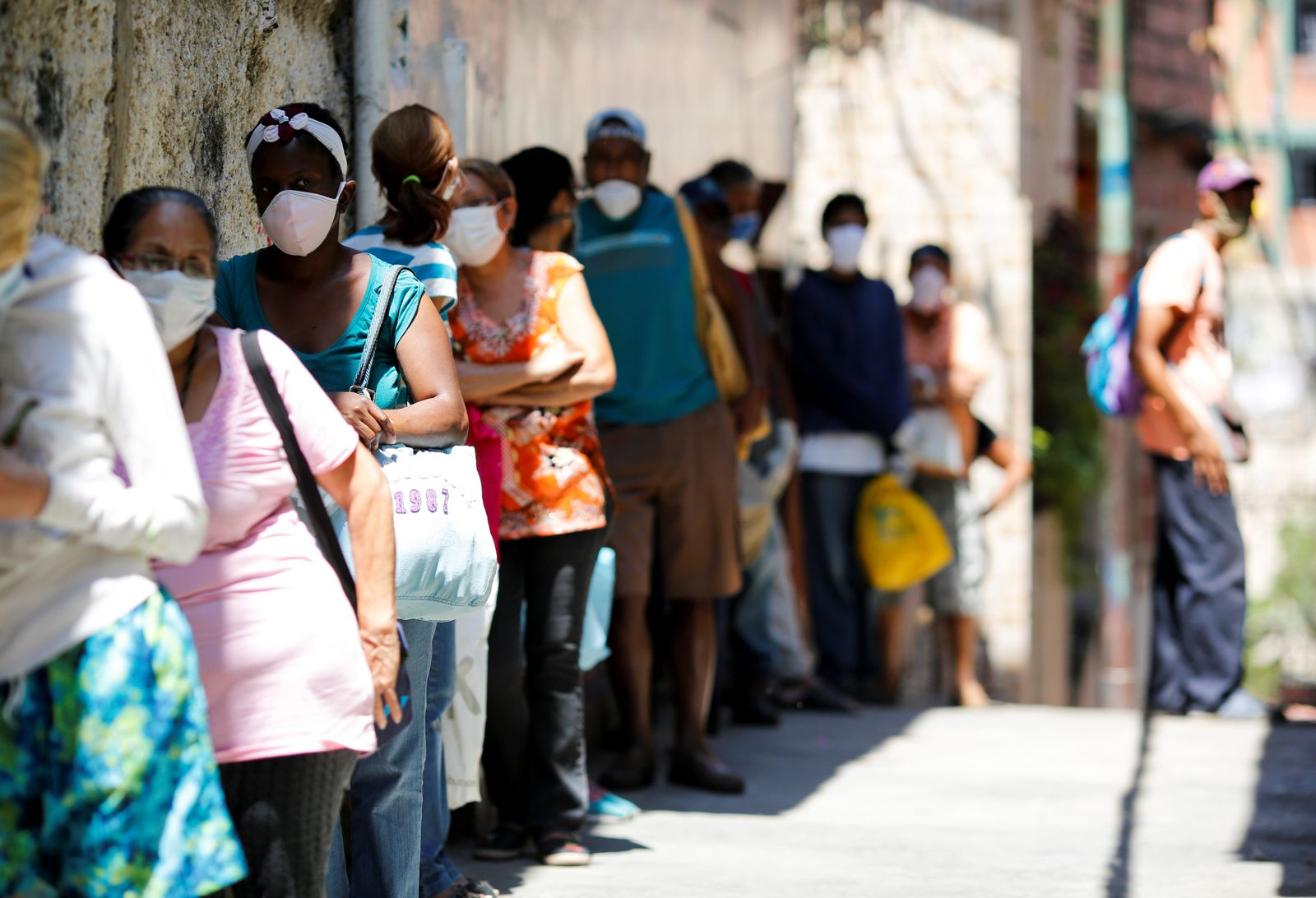 People make a line to receive food from a charity, in the slum of Carapita, during the nationwide quarantine due to the coronavirus disease (COVID-19) outbreak, in Caracas