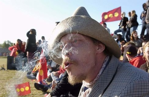 A Christiania supporter smokes while watching a soccer match between residents and the police.