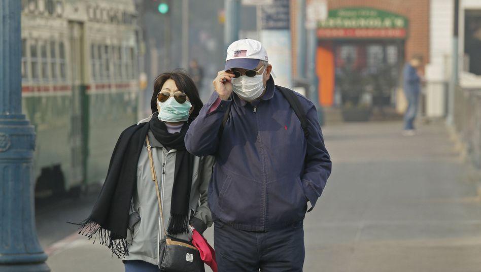 Ein Paar trägt Atemschutzmasken gegen den Rauch in San Francisco