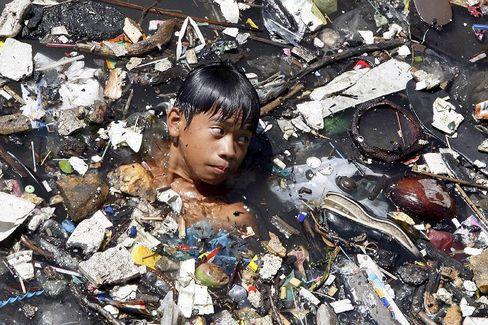 Philippinischer Junge im verschmutzten Fluss Wawa: Kinder in armen Ländern leiden am stärksten unter der Umweltzerstörung