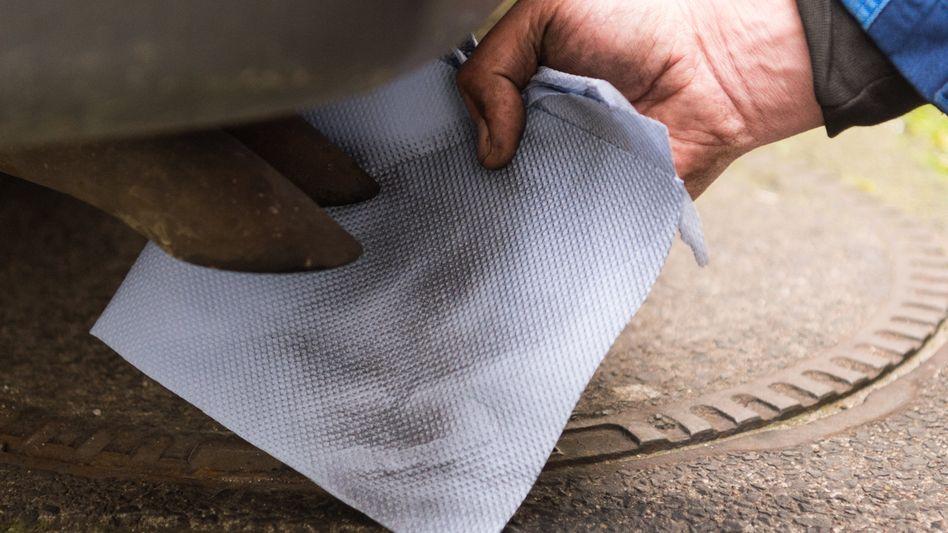 Ein Mechaniker hält ein Stück Papier vor einen Auspuff eines Dieselfahrzeugs