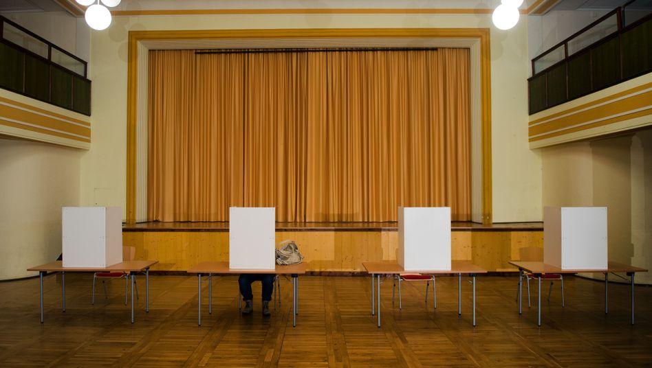 Vier Wahlkabinen und eine Wählerin