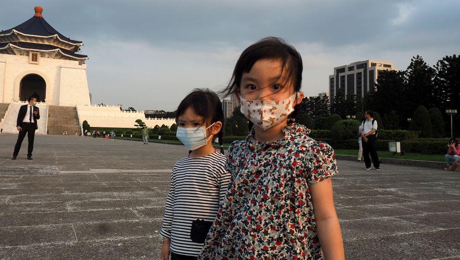 Zwei Mädchen mit Gesichtsmasken vor der Nationalen Chiang-Kai-shek-Gedächtnishalle in Taipeh