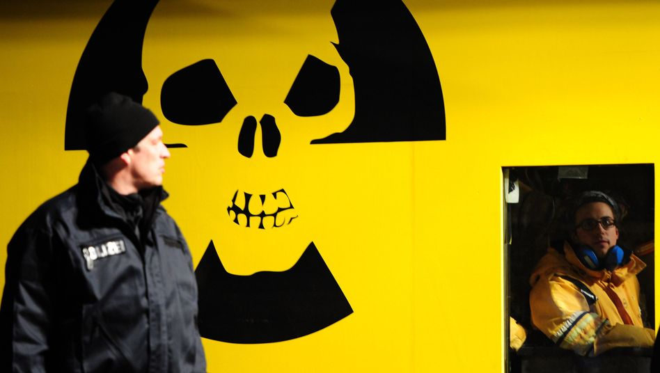 A Greenpeace activist, right, sits in a container blocking the Castor transport train in northern Germany.