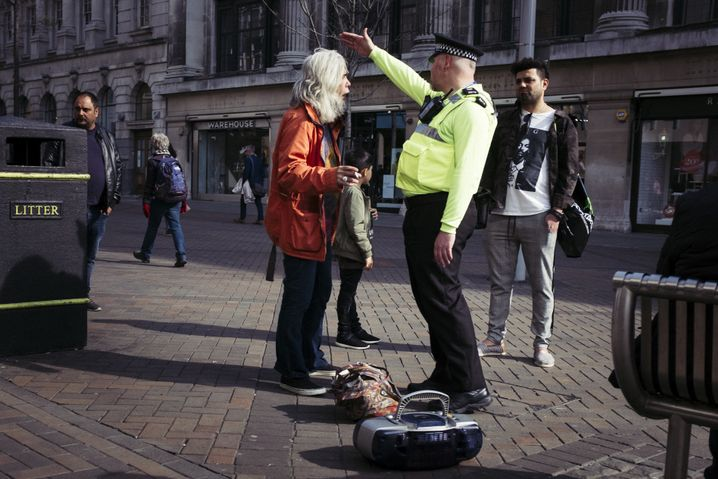 A police officer tells a man to leave the shopping street