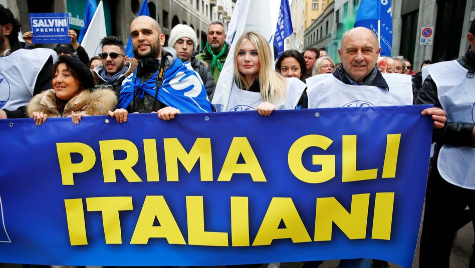 """Demonstrator's in Italy hold a sign reading """"Italians first."""""""