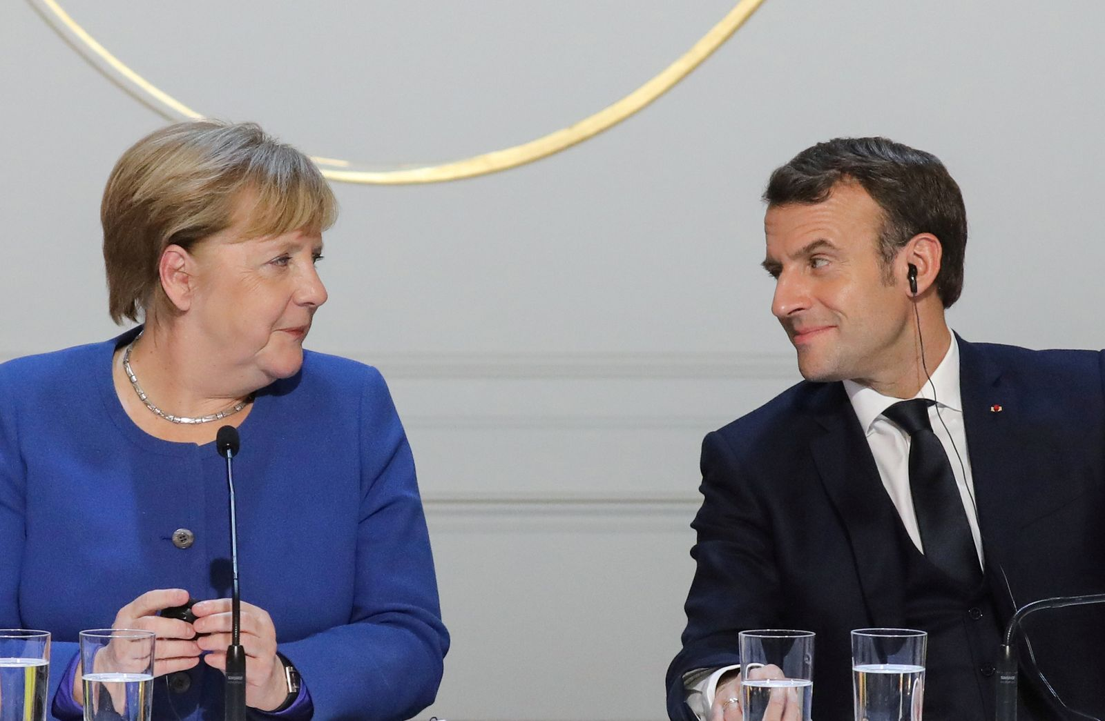 FILE PHOTO: German Chancellor Angela Merkel and French President Emmanuel Macron give a press conference after Ukraine summit