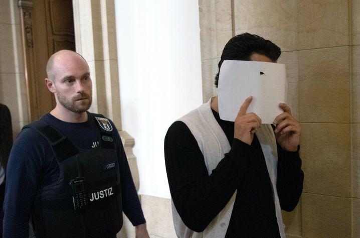 Nach dem Urteil: Einer der Angeklagten verlässt in Begleitung eines Justizbeamten nach dem Prozess das Gerichtsgebäude