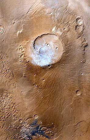 """Bewölkter Frühlingstag: Helle Wolkenfetzen hängen über dem Apollinaris Patera Vulkan, als der """"Mars Global Surveyor"""" im April 1999 dieses Bild aufnimmt"""