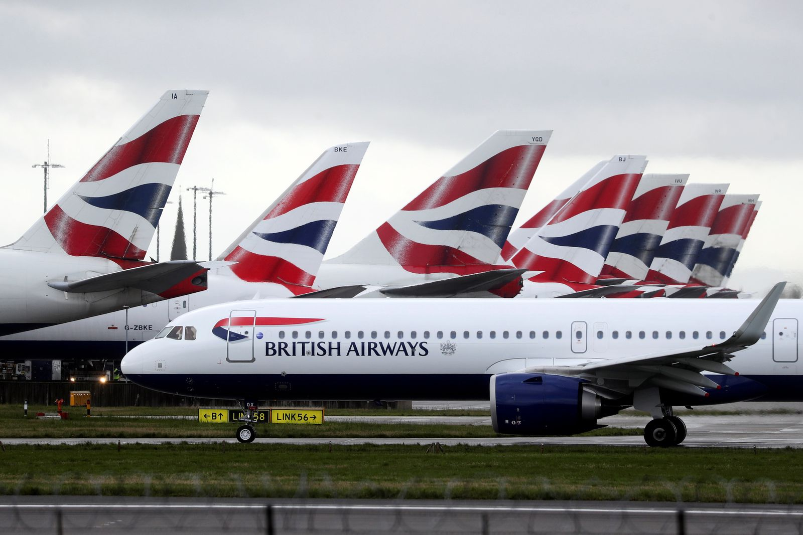 BA plane taxis past tail fins of parked aircraft to runway near Terminal 5 at Heathrow Airport