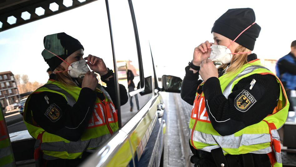 Eine Bundespolizistin in Baden-Württemberg zieht sich am Grenzübergang zur Schweiz vor einer Kontrolle eine Atemmaske auf