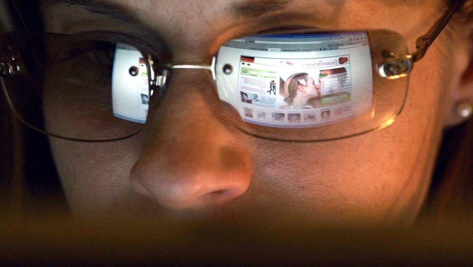 Vor dem Computer: Eine Frau betrachtet eine Dating-Website