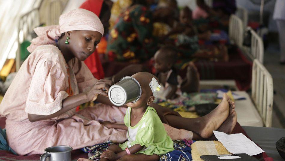 Mutter füttert unterernährtes Kind in Nigeria