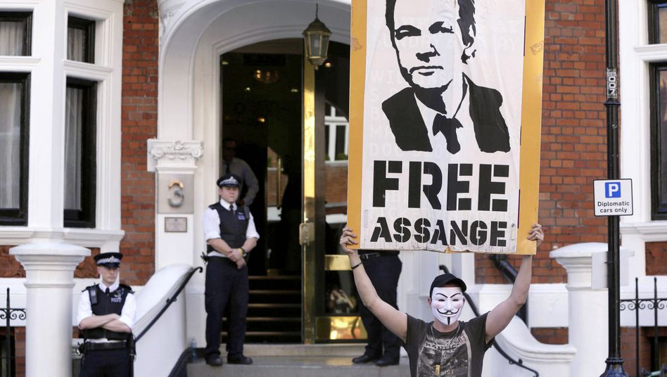 A protestor holds a poster of Wikileaks founder Julian Assange outside Ecuador's embassy in London.