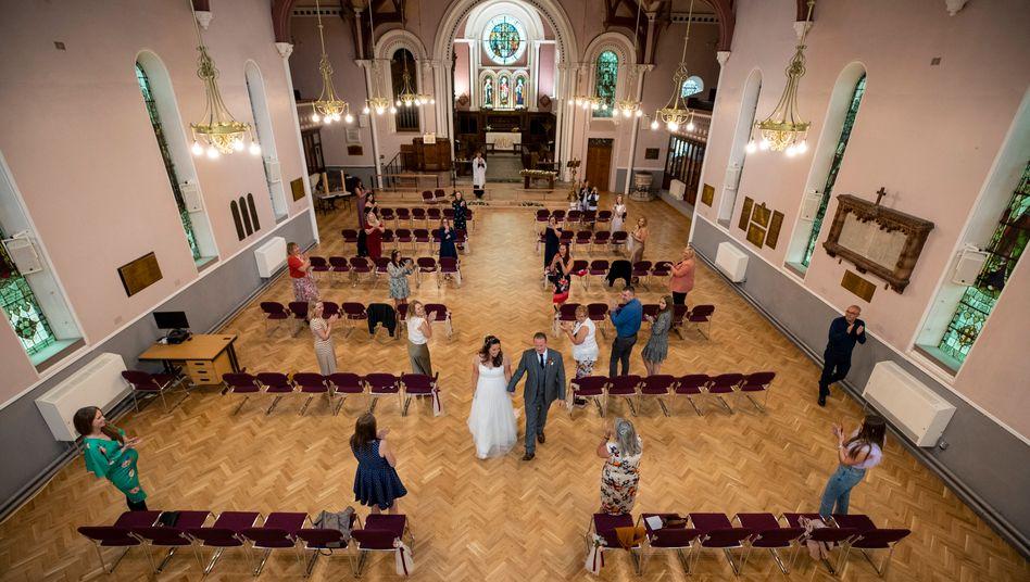 Ein Brautpaar schreitet durch eine Kirche - die Gäste halten Abstand