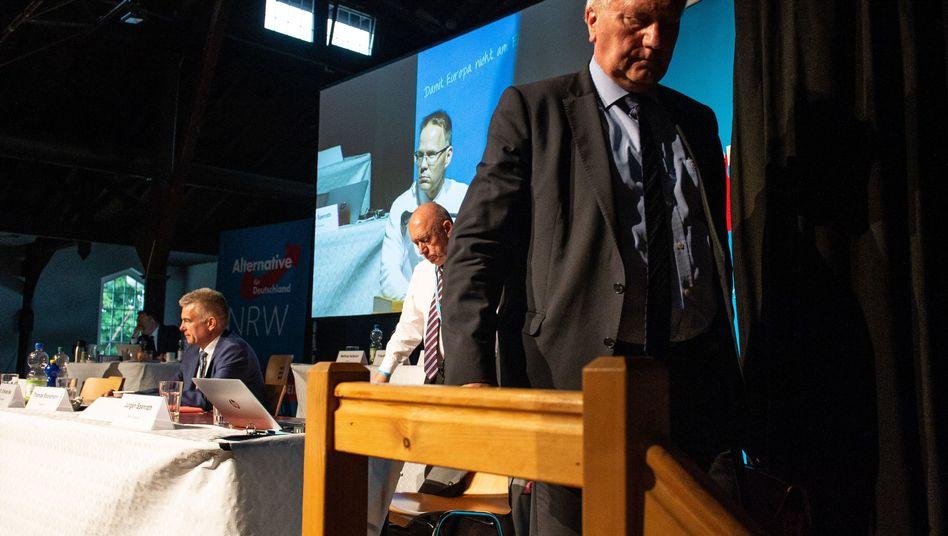 Helmut Seifen (r), bisheriger Landesvorsitzender der NRW-AfD, verlässt nach seinem Rücktritt das Podium beim Landesparteitag der nordrhein-westfälischen AfD. Links sitzt Thomas Röckemann, bisher Seifens Co-Landesvorsitzender.