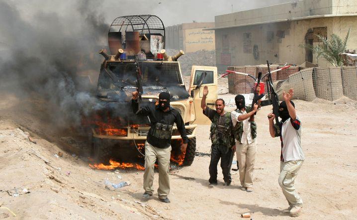 Kämpfer der Mahdi-Armee im März 2008 vor einem zerstörten Fahrzeug in Bagdad