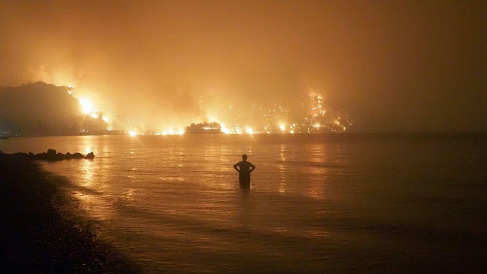 Ein Mann beobachtet einen Waldbrand auf der griechischen Insel Euböa