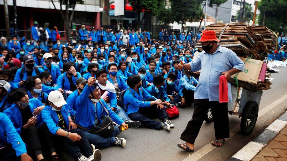 Studierende blockieren am Donnerstag eine große Straße in Indonesiens Hauptstadt Jakarta, um gegen die geplante Arbeitsmarktreform zu demonstrieren