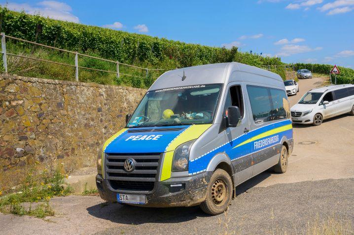 Ein polizeiähnlicher Transporter mit der Aufschrift »Friedensfahrzeug« am Rand des Katastrophengebiets