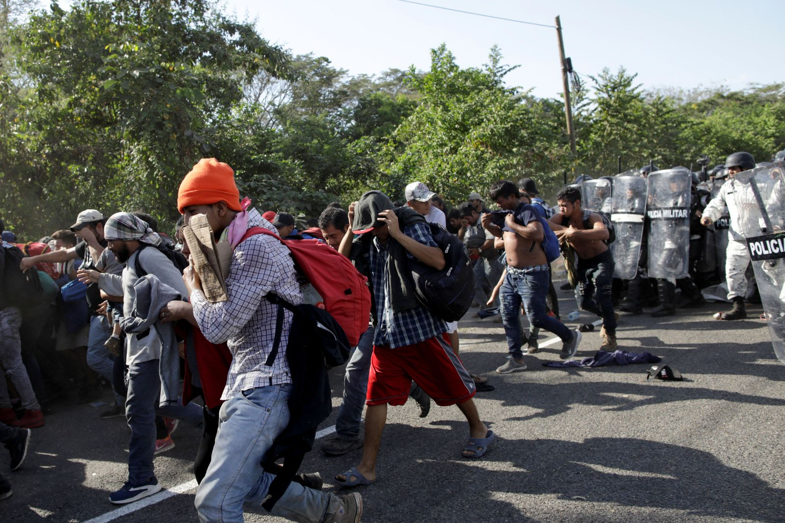 Migrants, mainly from Central America and marching in a caravan, react as members of the security forces approach them, near Frontera Hidalgo, Chiapa