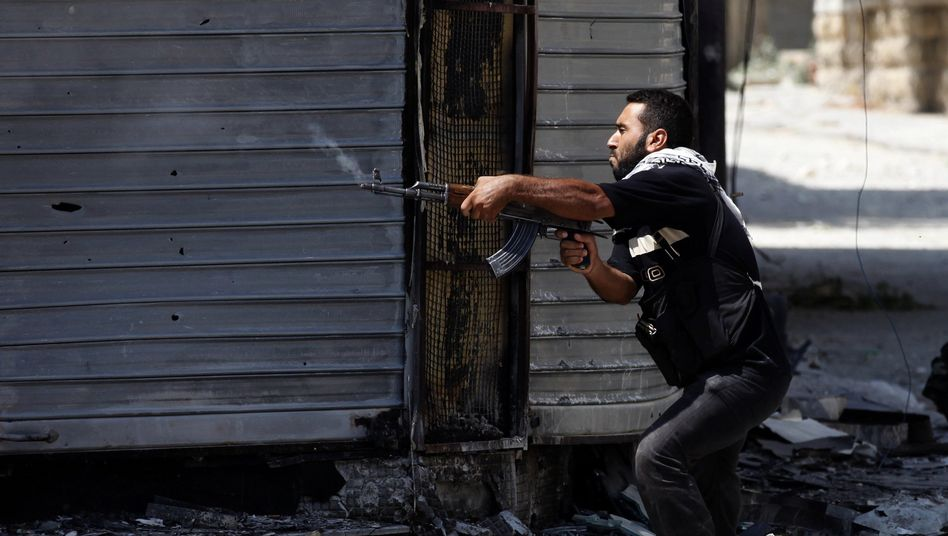 A Free Syrian Army fighter fires an AK-47 rifle in Aleppo, Syria, on Aug. 15, 2012.