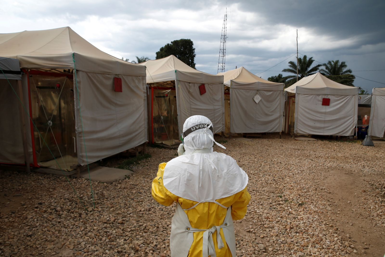 A health worker wearing Ebola protection gear, walks before entering the Biosecure Emergency Care Units at the Alima Ebola treatment centre in Beni