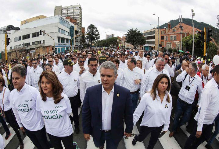 Duque (M.) mit seiner Frau (rechts von ihm) und seiner Stellvertreterin (links von ihm) beim Protestmarsch in Bogotá