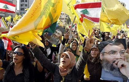 Hezbollah leader Sheikh Hassan Nasrallah, pictured here on placards at a rally in Beirut last week, could gain from a prisoner exchange.