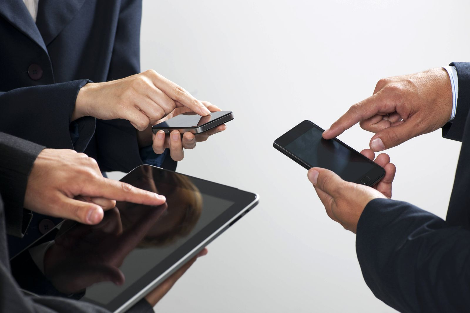 Colleagues exchanging information with smartphones and digital tablet cropped PUBLICATIONxINxGERxSU